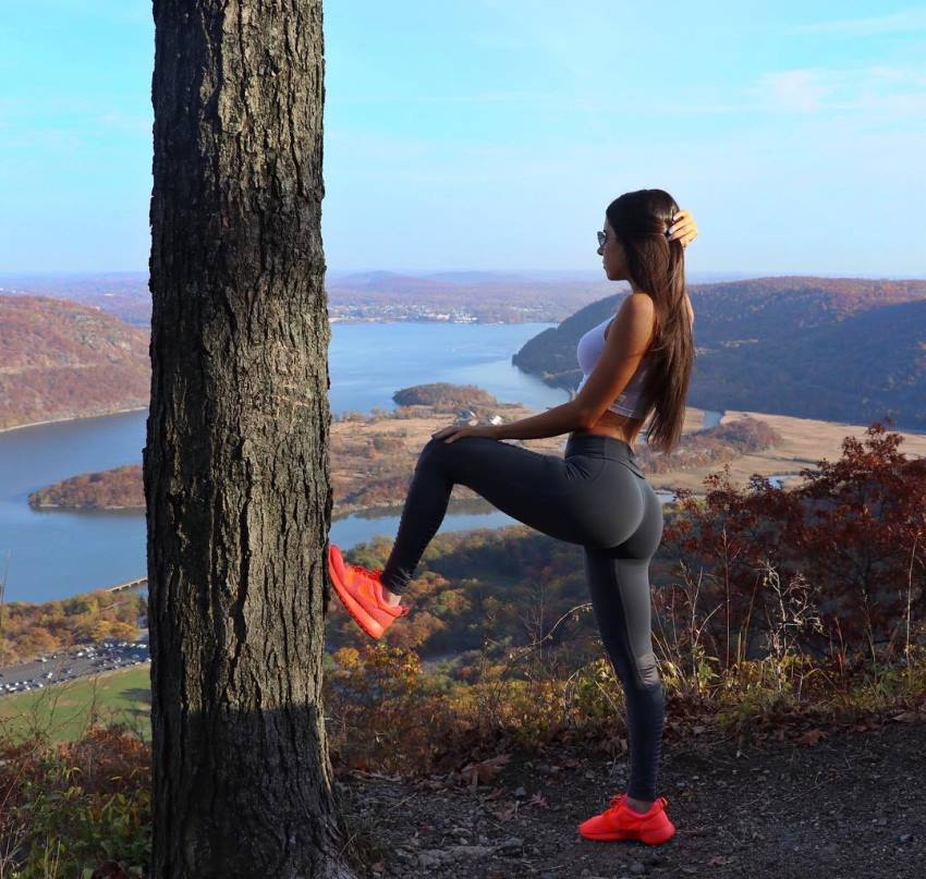 Jen Selter standing on the hill by a tree, showcasting her glutes in black leggings