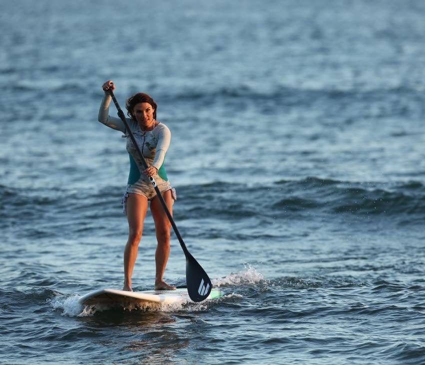 Lauren Abraham paddle-surfing in the sea