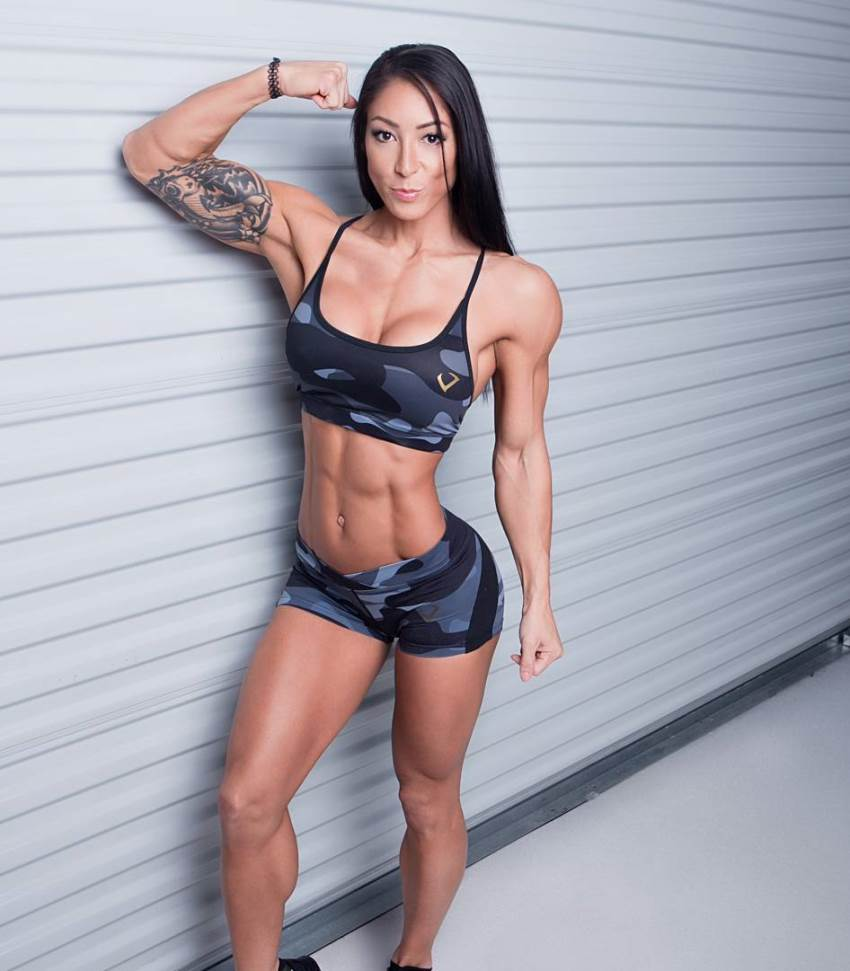 Lori Slayer flexing her biceps for a camera, looking lean and fit