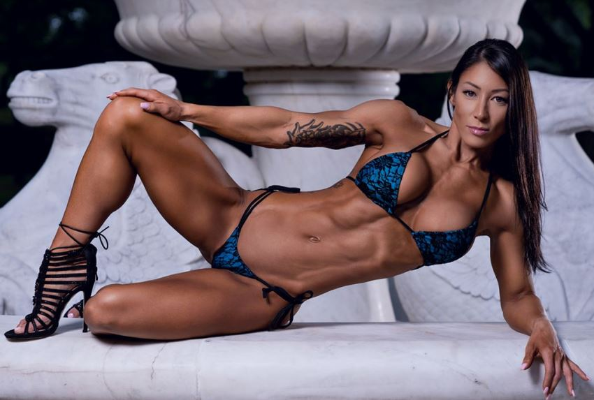 Lori Slayer lying down, posing for a photoshoot, looking ripped and muscular