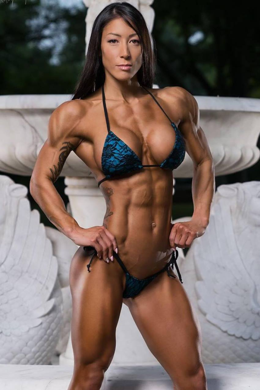 Lori Slayer posing for a photo in a blue bikini, looking stage ready
