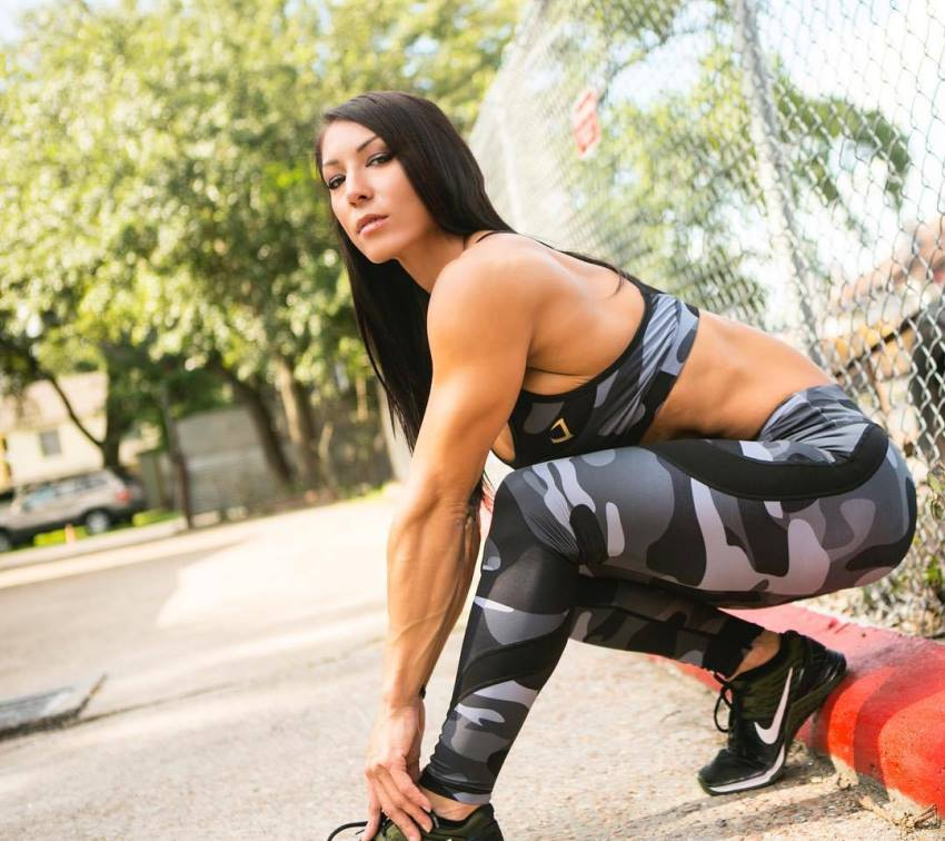 Loris Slayer tying her shoe outdoors, wearing camouflaged leggings