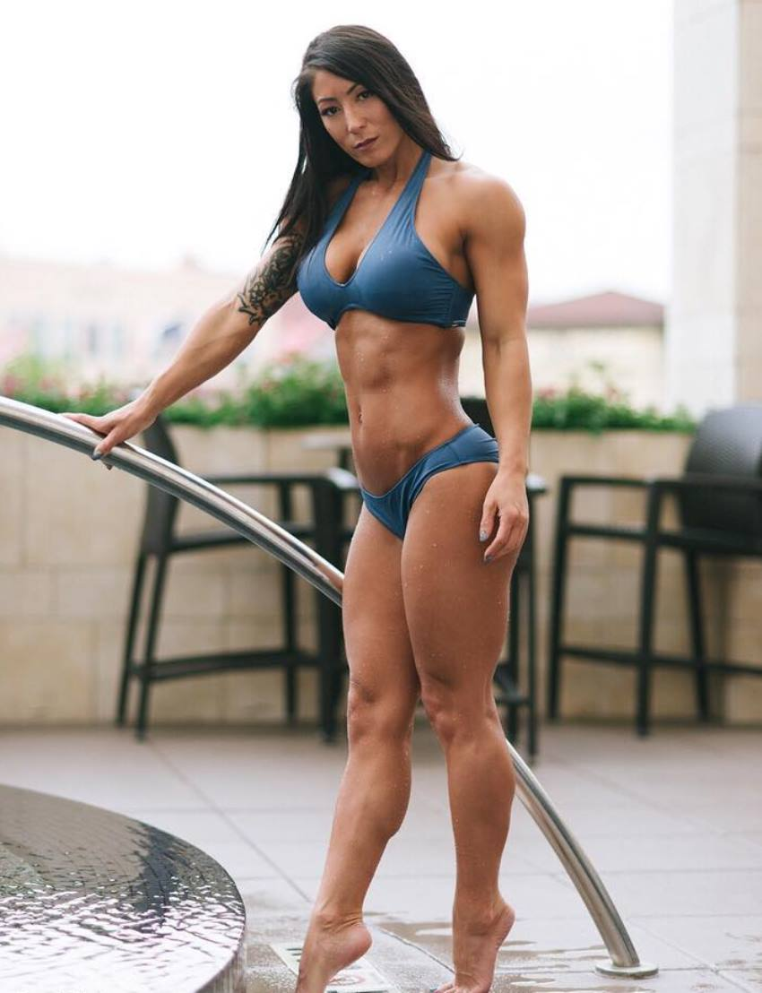 Lori Slayer standing on her toes by the pool in a blue bikini, looking lean and fit