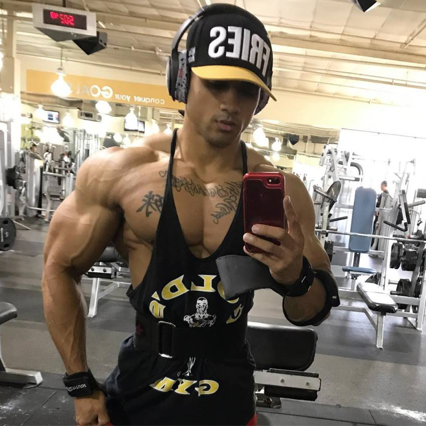 Marvin Moss III taking a photo of his ripped physique in a gym
