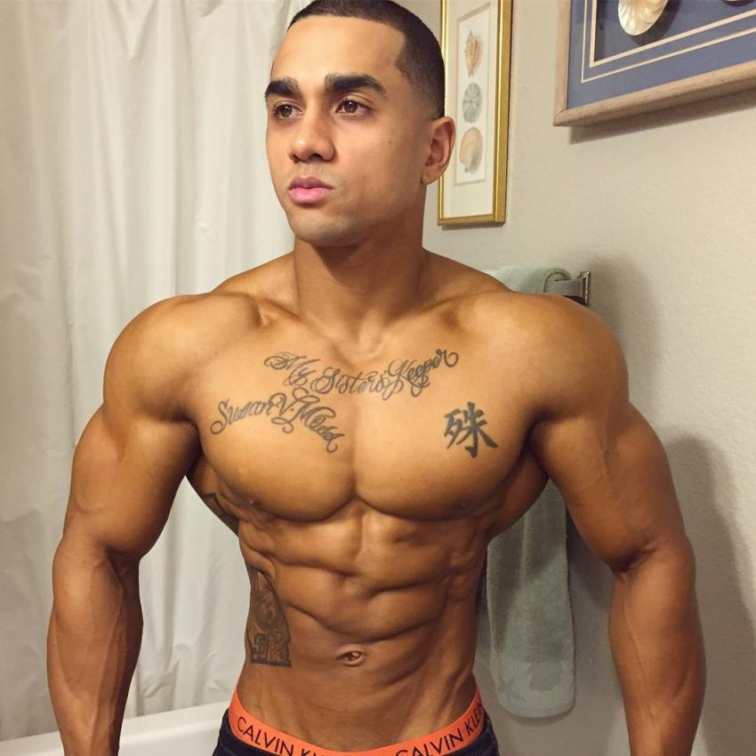 Marvin Moss III in the bathroom, posing for a picture, looking ripped and aesthetic