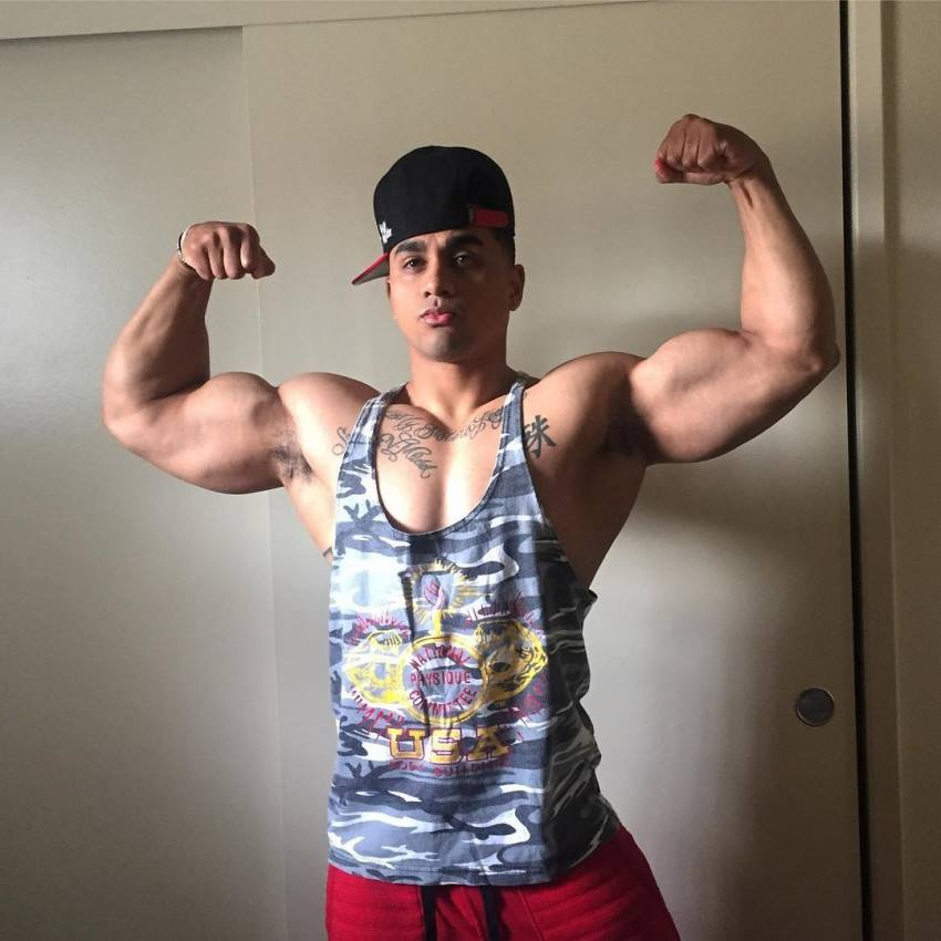 Marvin Moss III doing a front double biceps pose with a hat and a tank top on
