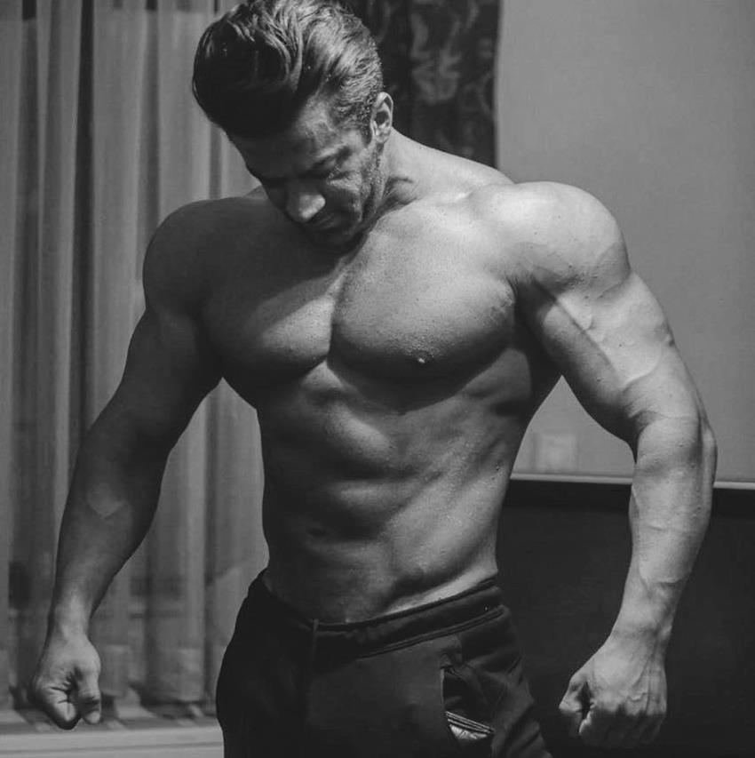 Mohammad Kashanaki posing shirtless in a room, looking massive and ripped