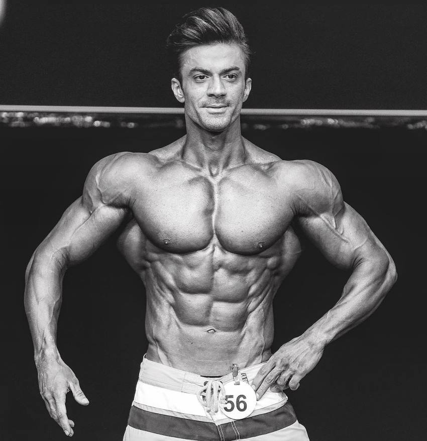 Black and white picture of Mohammad Kashanaki on the men's physique stage, looking ripped and muscular