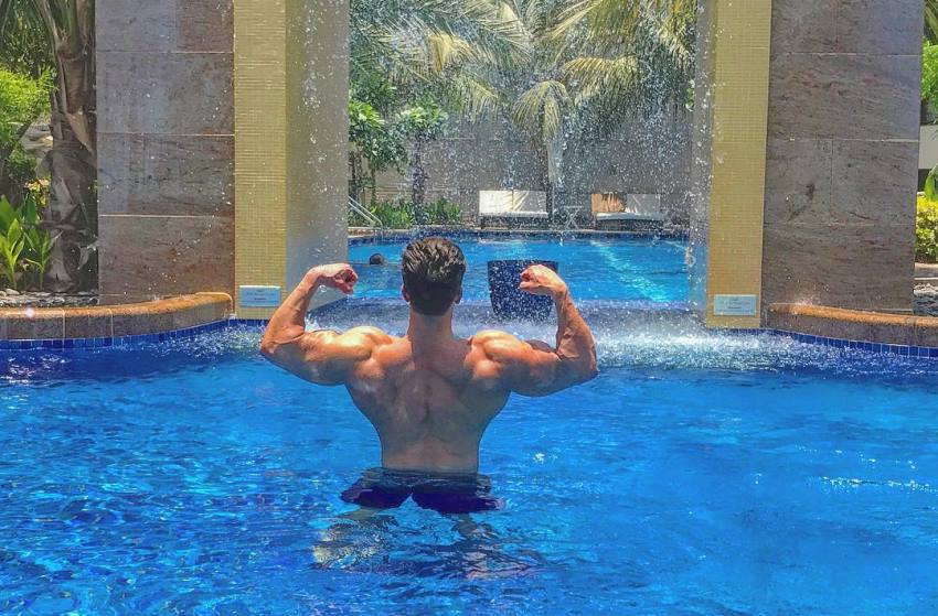 Mohammad Kashanaki doing a back double biceps pose while being shirtless in a pool
