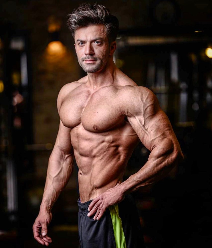 Mohammad Kashanaki posing for the picture, showing his ripped arms and shoulder, chest, abs, and obliques