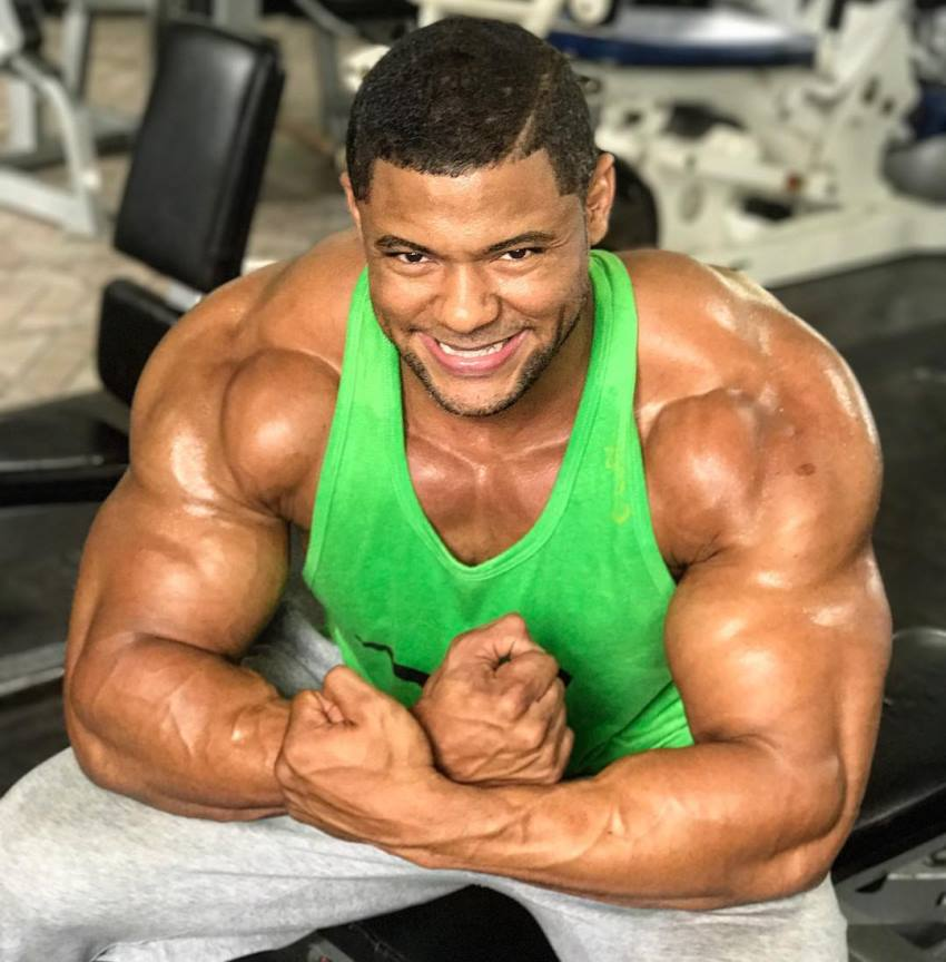 Robert Galva sitting on a bench in the gym, flexing his muscular arms