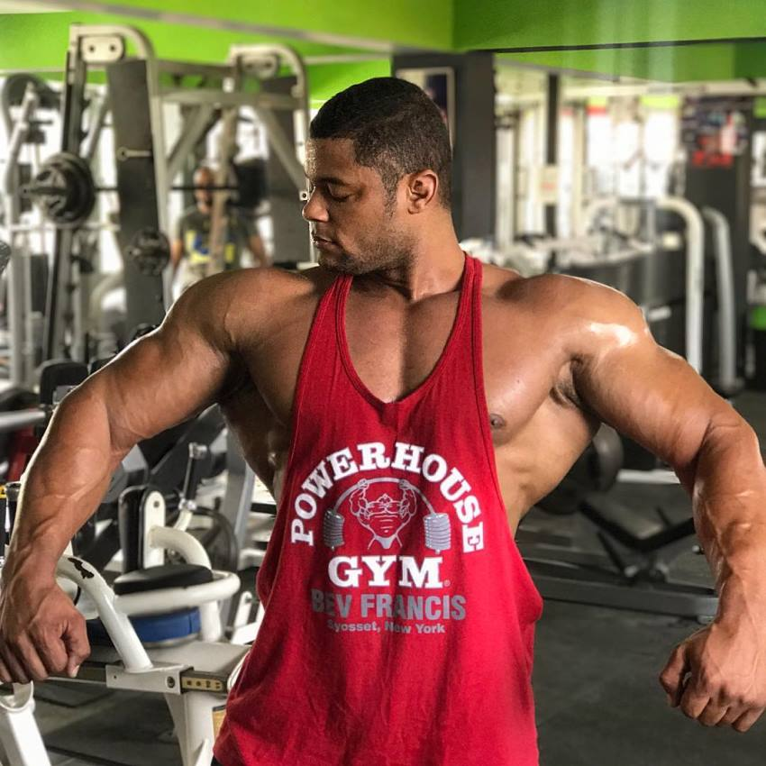 Robert Galva standing in a gym in a red tank top, spreading his arms and lats