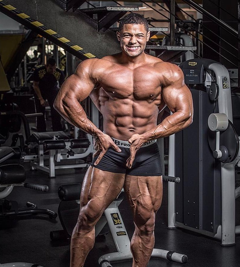 Robert Galva posing shirtless in the gym, flexing his arms, legs, chest, and abs