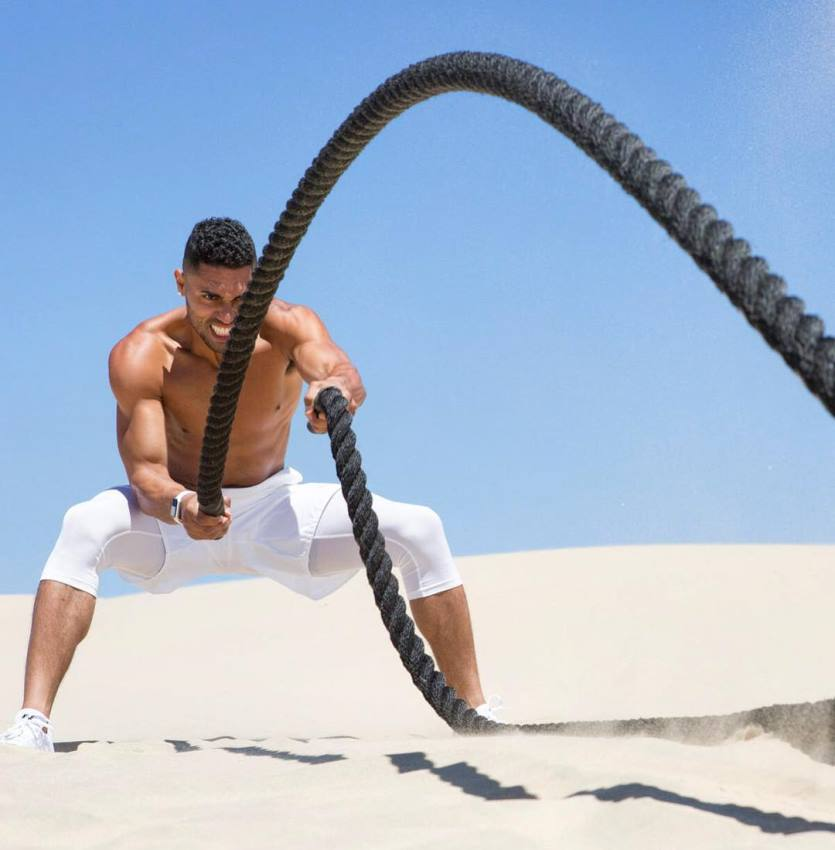 Ryan Tremaine Klarenbach exercising with ropes on the sand