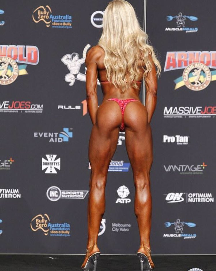 Sara Back flexing her back legs and glutes on the bikini fitness stage