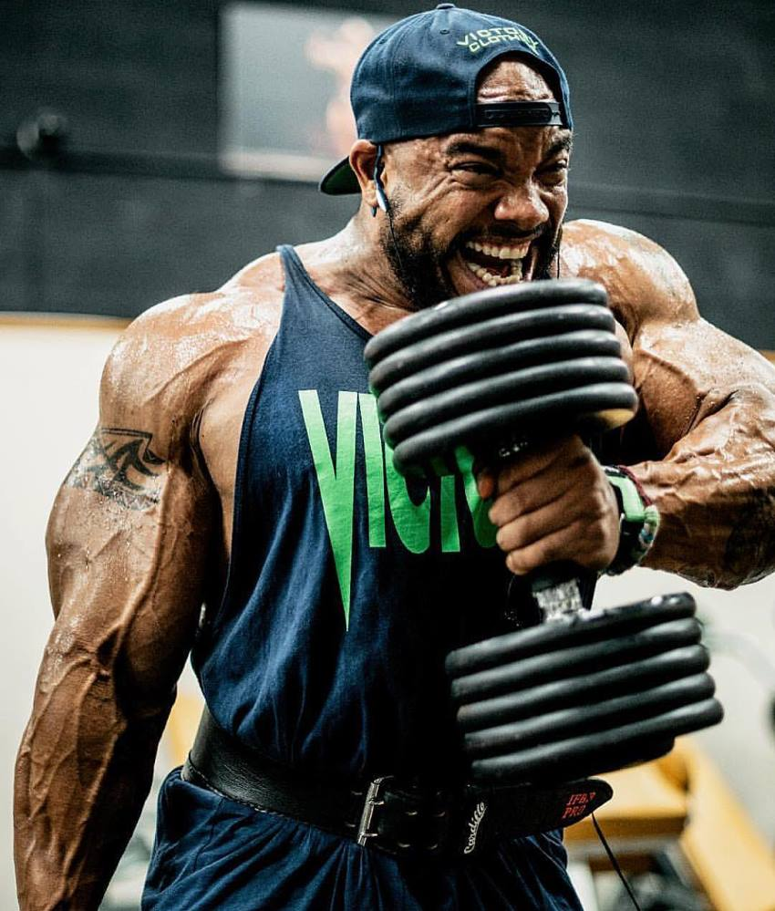 Sergio Oliva Jr doing hammer curls with a pained grimace