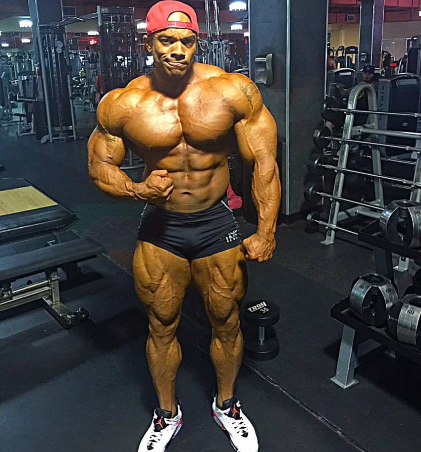 Sergio Oliva Jr posing shirtless in the gym, looking big and ripped