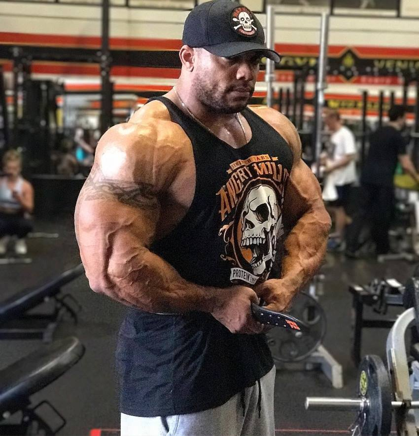Sergio Oliva Jr flexing his arms in the gym
