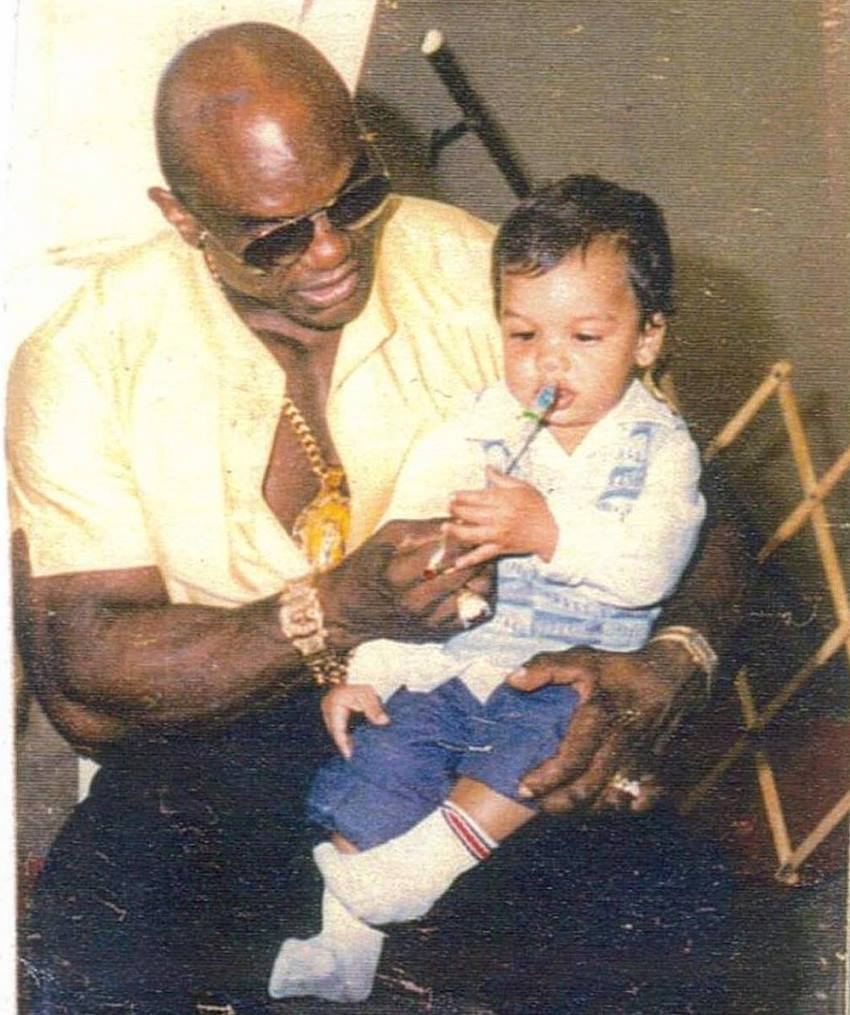 Sergio Oliva Jr when he was a child, sitting in his father's lap