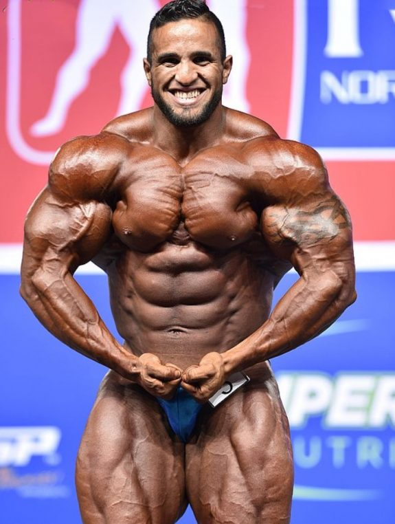 Abdelaziz Jellali flexing his muscles in a bodybuilding contest in front of an audience