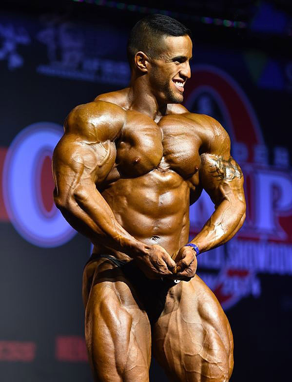 Abdelaziz Jellali in a most muscular pose on the stage in front of the audience
