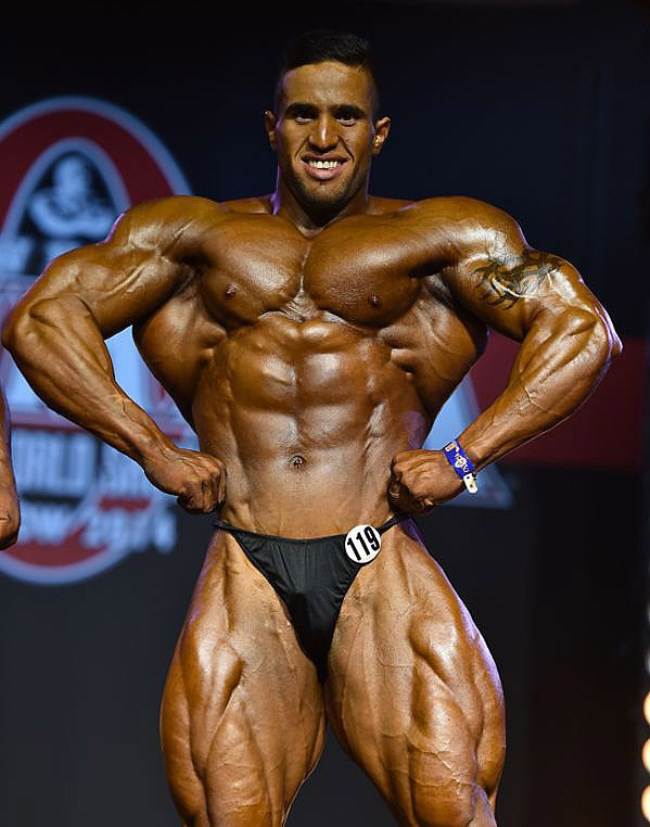 Abdelaziz Jellali spreading his lats in front of the judges on the stage