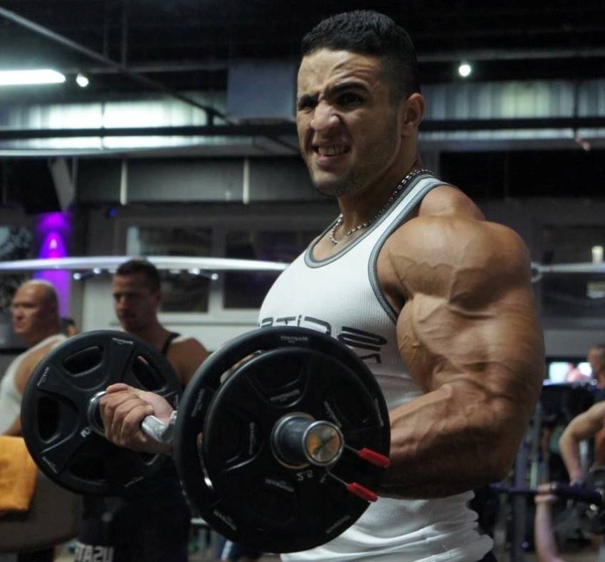 Abdelaziz Jellali doing ez-bar biceps curls in the gym, his arms looking vascular and big