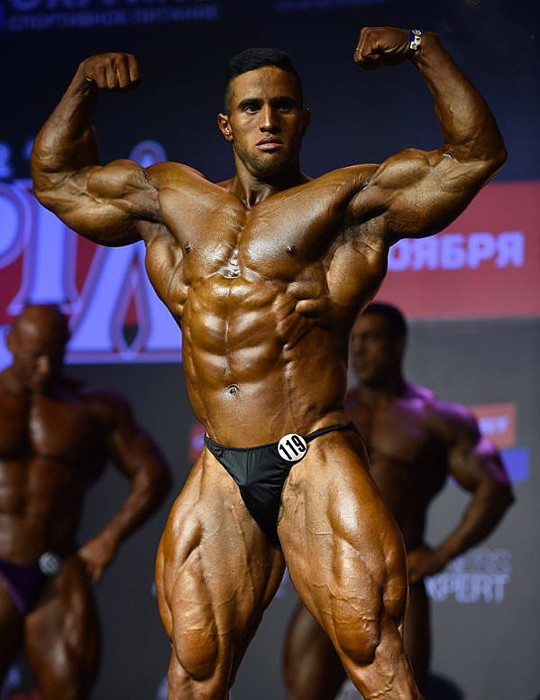 Abdelaziz Jellali doing a front double biceps flex at the stage