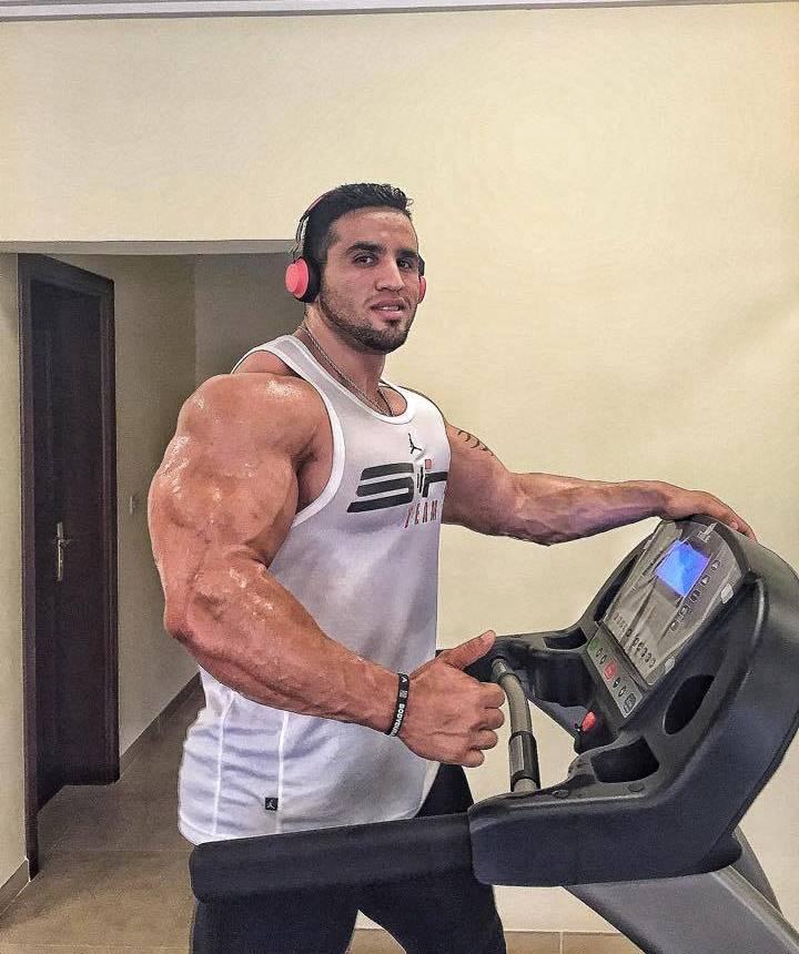 Abdelaziz Jellali doing cardio on a treadmill, his arms looking massive