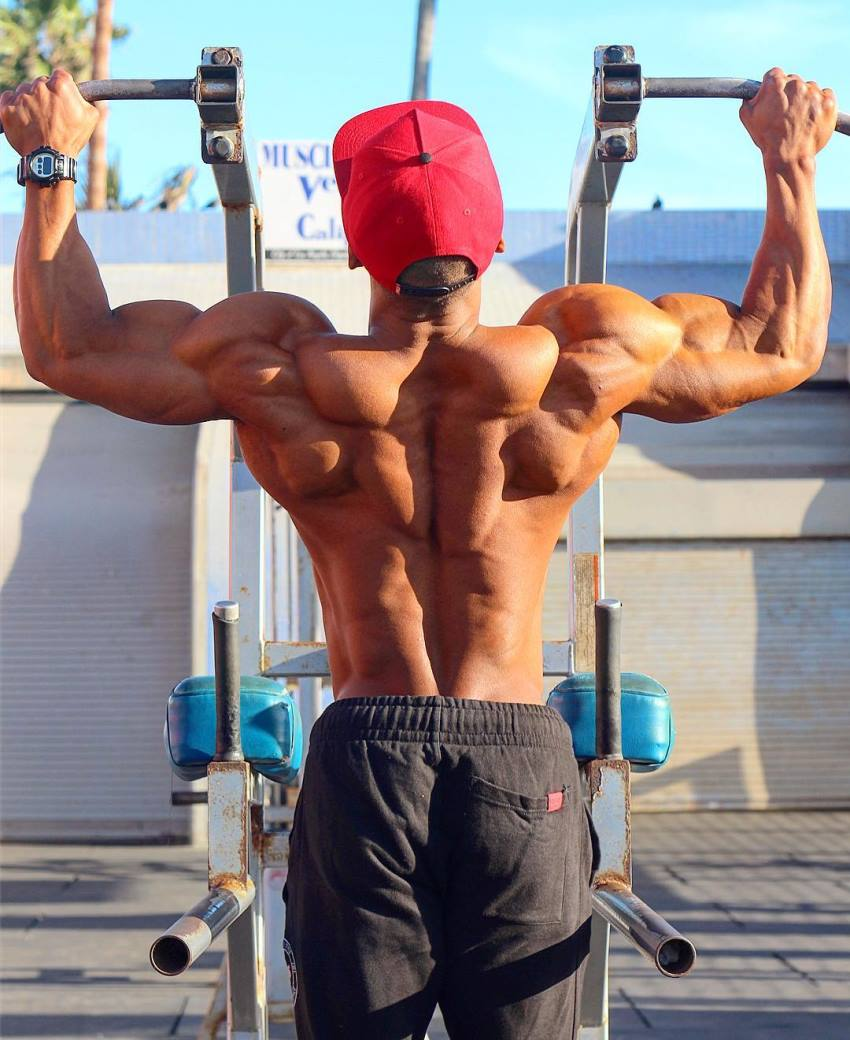 Ahmad DeGuzman doing pull ups, his back looking ripped and muscular