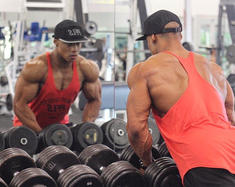 Ahmad DeGuzman looking at himself in the mirror while holding dumbbells