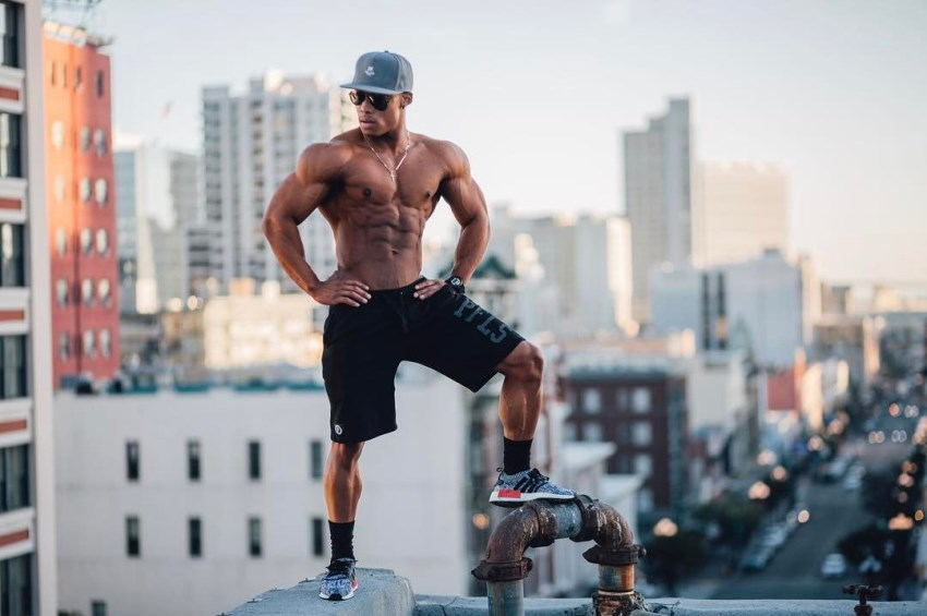Ahmad DeGuzman standing shirtless on top of a skyscraper