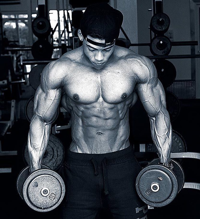 Ahmad DeGuzman holding two dumbbells and looking down, being shirtless, and looking ripped