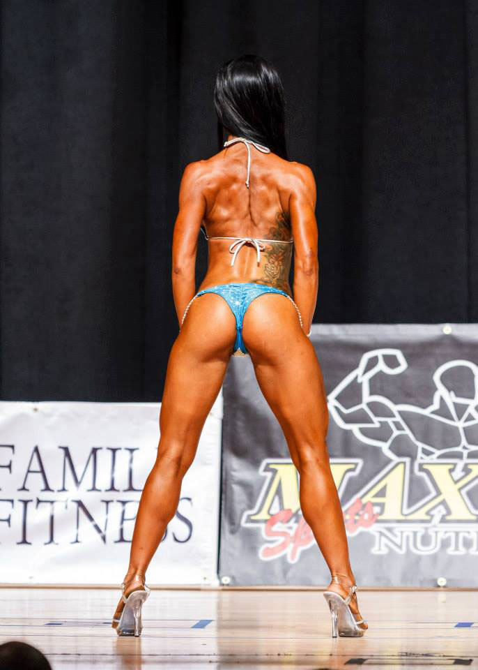 Alysia Macedo on stage at a bodybuilding competition showing off her back and glutes.