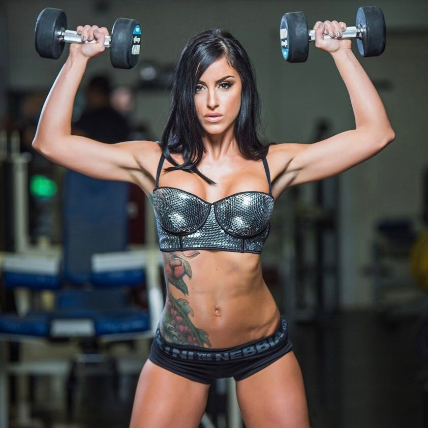 Alysia Macedo holding up dumbbells in the gym.