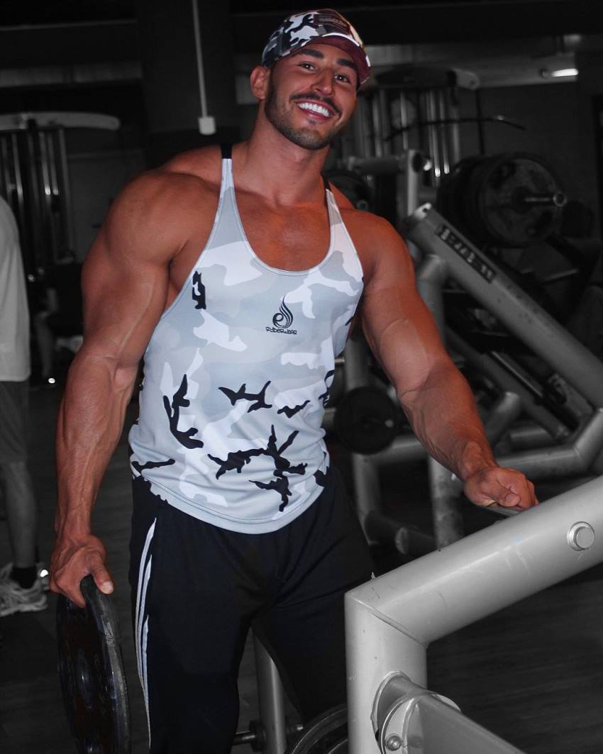 Amin Elkach in the gym in a grey tank top, smiling at the camera