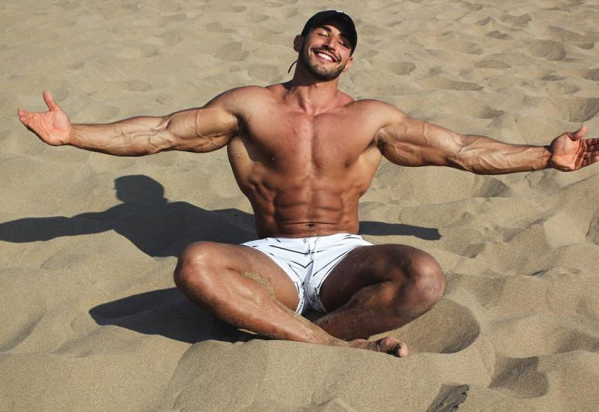 Amin Elkach sitting shirtless on the sand and soaking up the sun