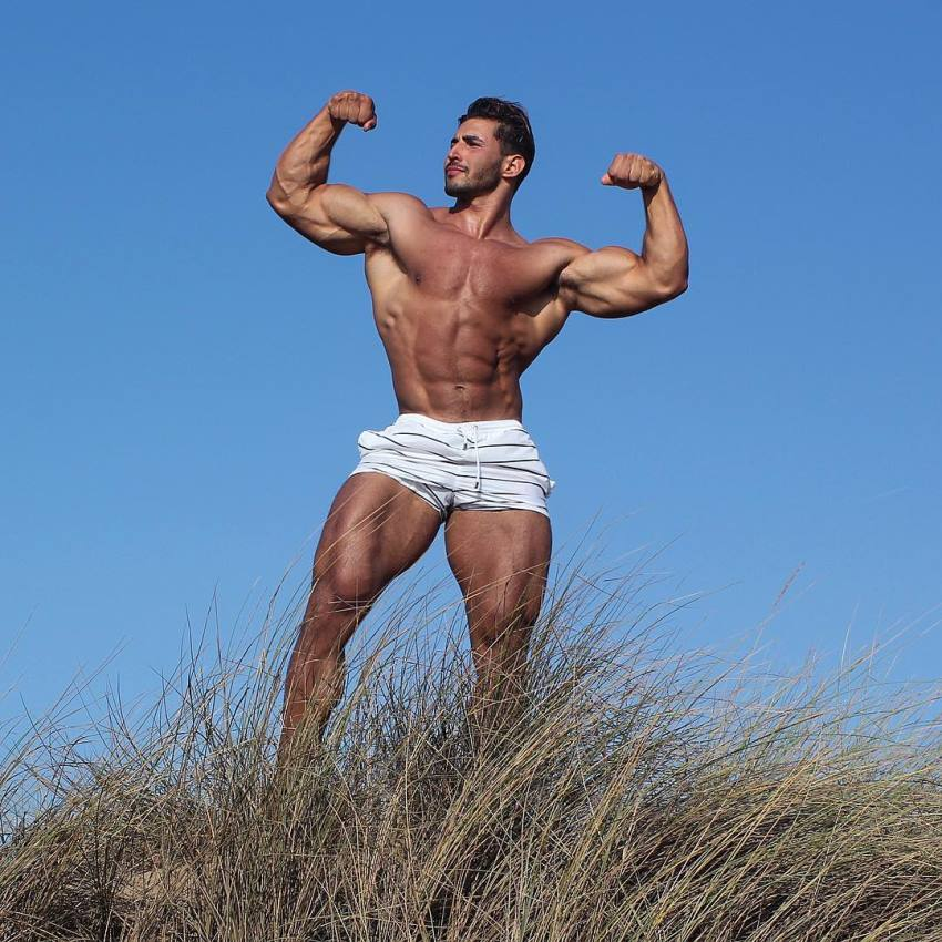 Amin Elkach doing a shirtless front double biceps flex outdoors
