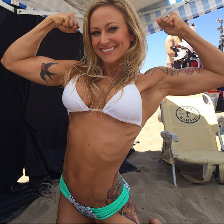Amy Updike flexing her arms on the beach.