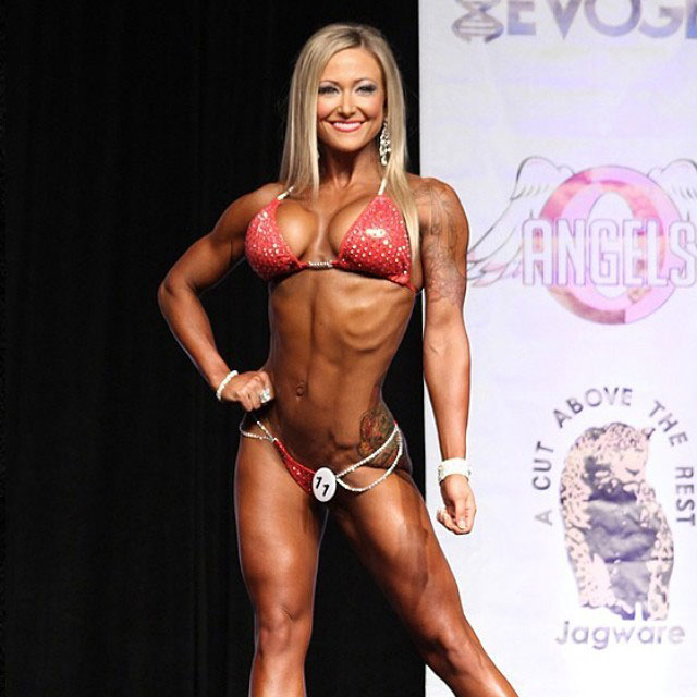 Amy Updike posing on stage at a bikini competition,.