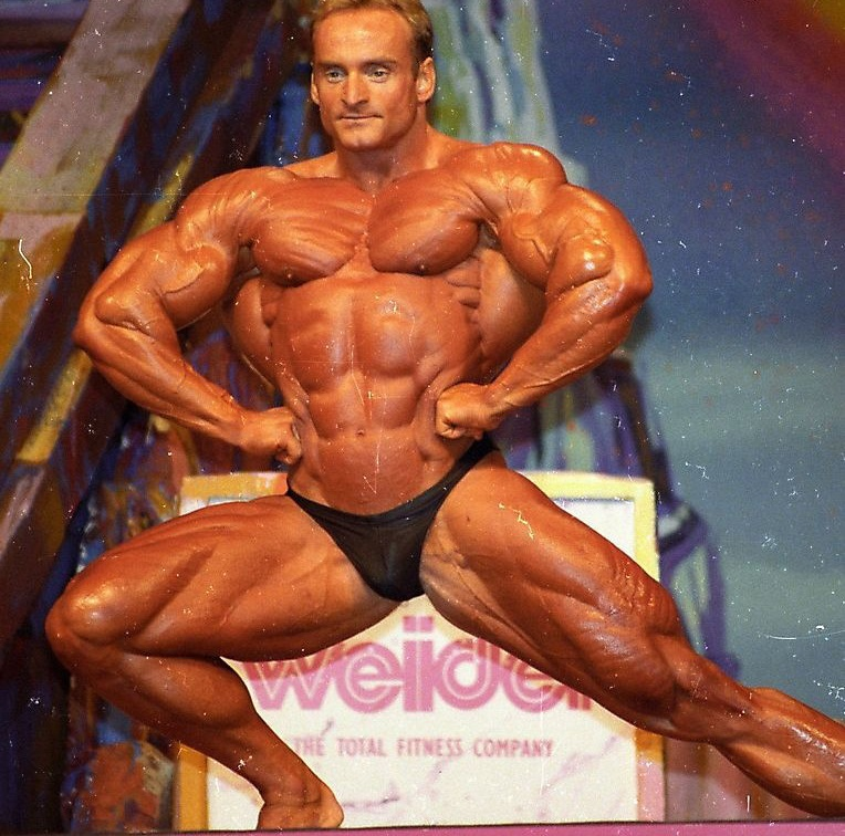 Andreas Munzer spreading his lats wide on the stage, and showcasting his ripped physique