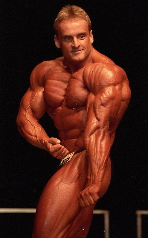 Andreas Munzer flexing his arms, chest, and shoulders on the stage, showing his outstanding physique to the judges