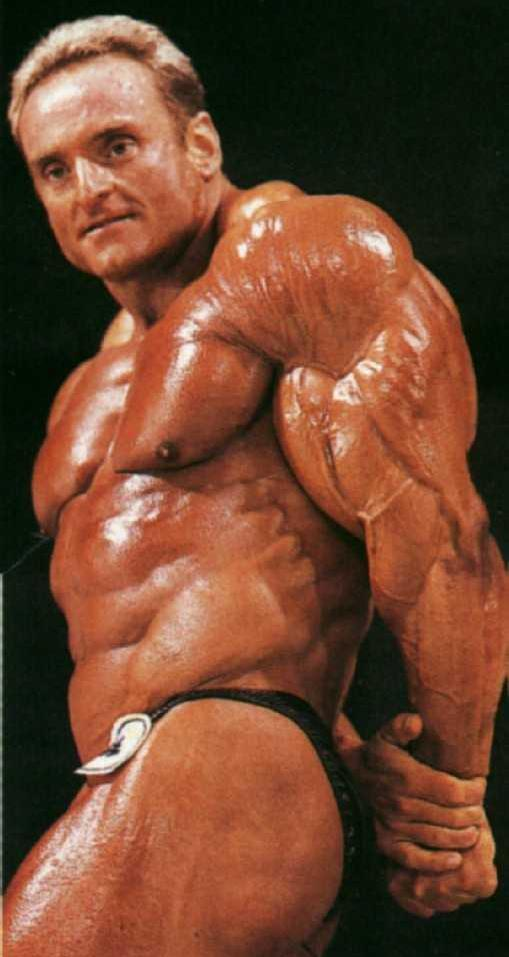 Andreas Munzer flexing his triceps on the stage