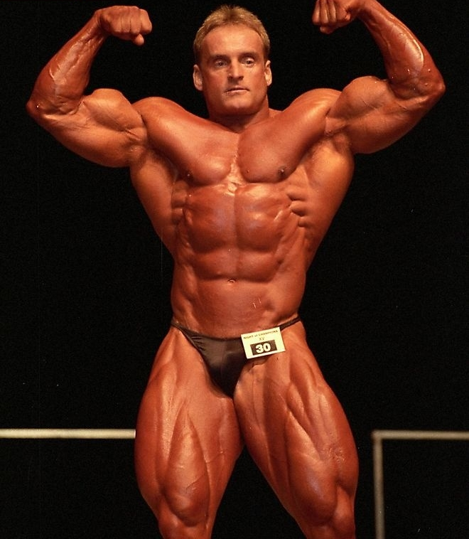 Andreas Munzer doing a front double biceps pose on the stage