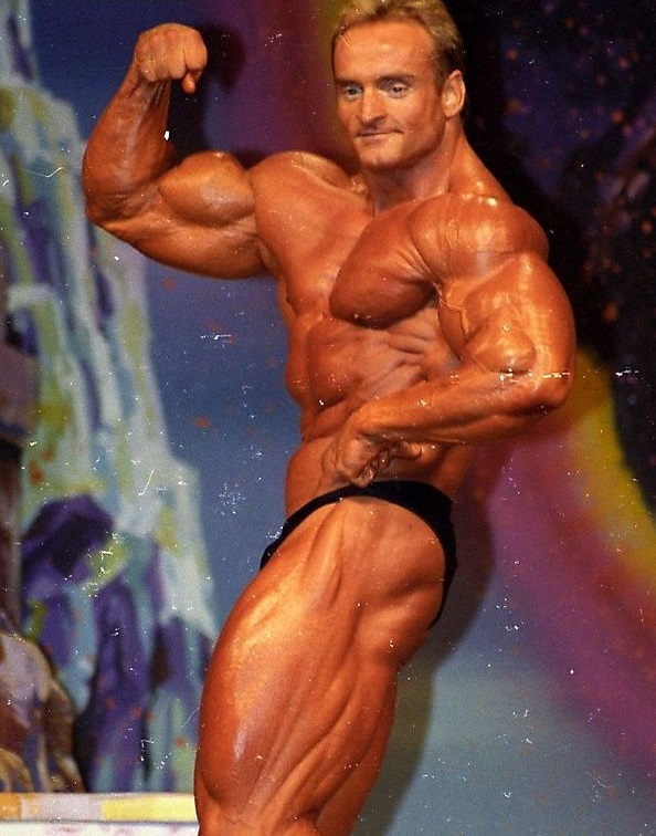 Andreas Munzer flexing his biceps on the stage