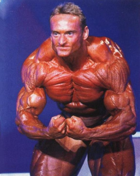 Andreas Munzer doing the most muscular pose on the stage, looking incredibly ripped