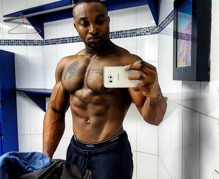 Antonio Mitchell taking a selfie of his muscular chest, arms, and chiseled abs