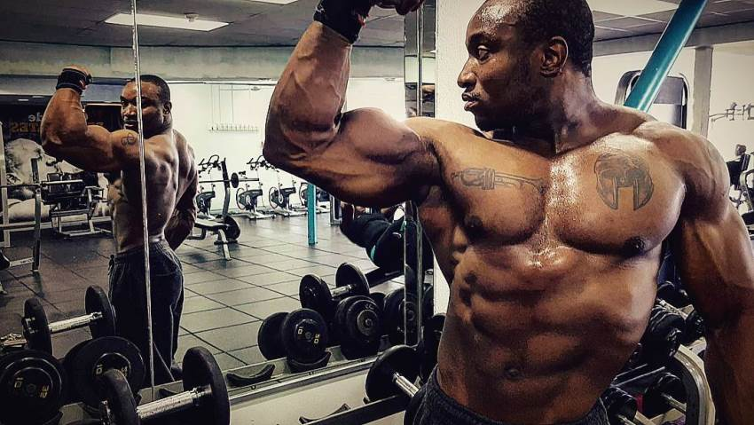 Antonio Mitchell posing shirtless in the gym, doing biceps flex in the mirror