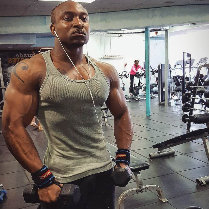 Antonio Mitchell showing his ripped physique in a grey tank top in the gym