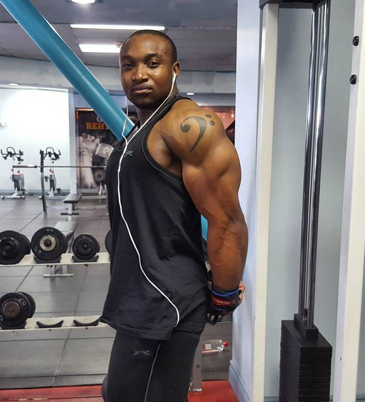 Antonio Mitchell flexing his ripped triceps in the gym